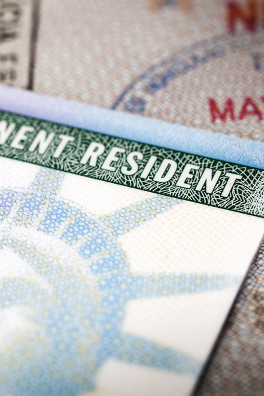 Una tarjeta de residencia reposa sobre un pasporte.
