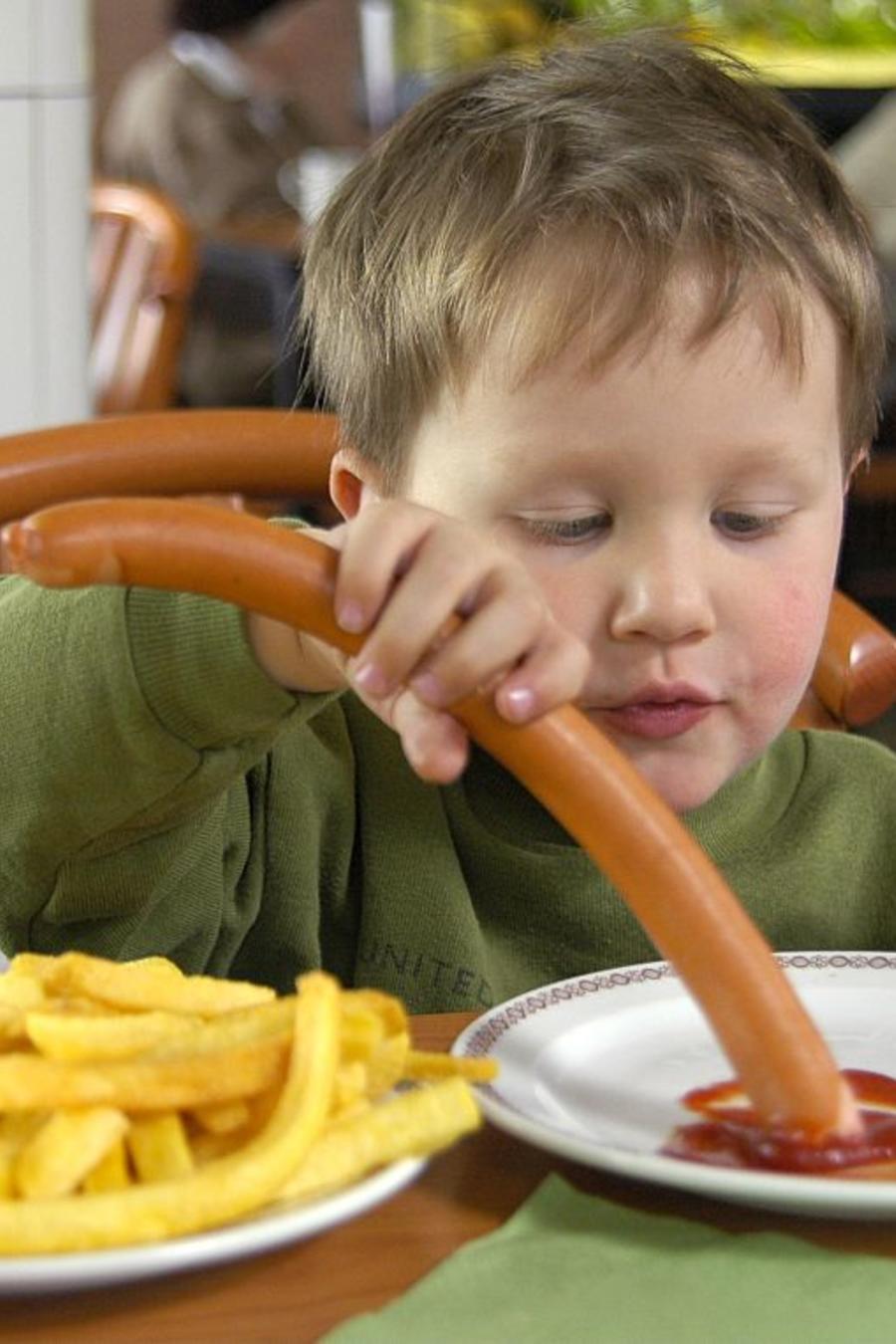 Kind isst in einem Schnellrestaurant Pommes frites und Wiener Wuerstchen mit Ketchup