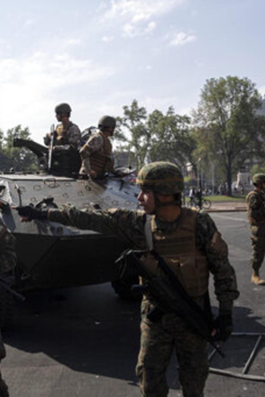 Una mujer muestra una foto de una persona desaparecida en la dictadura militar de Chile ante los soldados desplegados este sábado en la capital, Santiago.