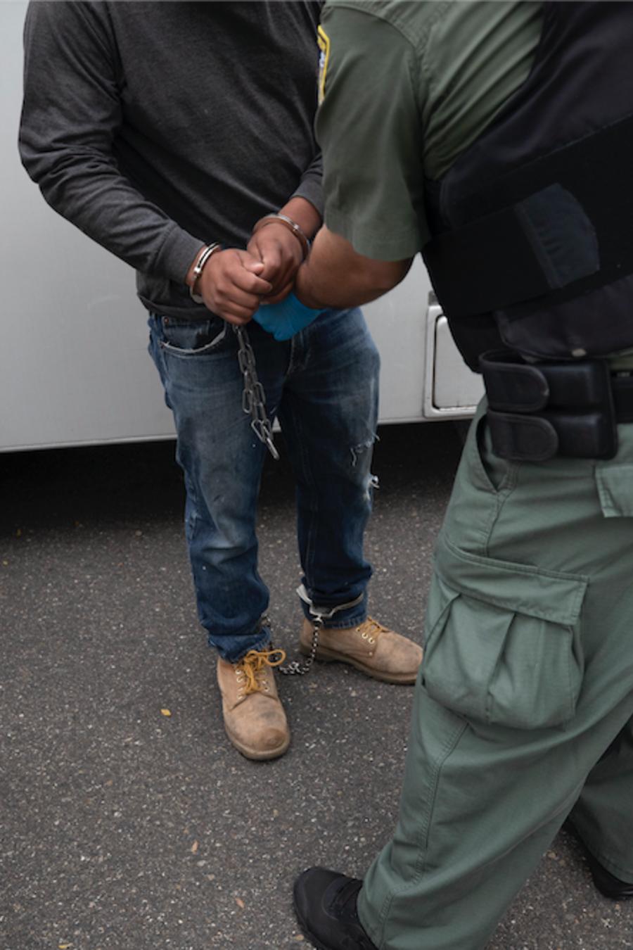Un oficial de ICE transfiere a un hombre esposado durante una operación en Escondido, California, el 8 de julio de 2019.