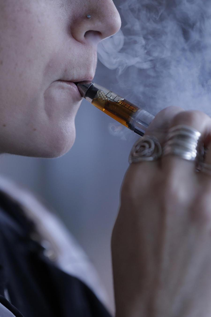 Una joven utiliza un cigarrillo electrónico.