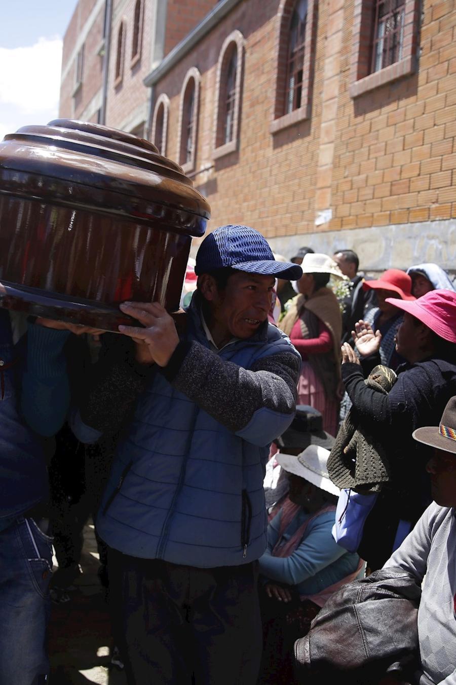 Personas llevan a hombros el ataúd de uno de los fallecidos del pasado martes en un episodio de violencia en El Alto, Bolivia.