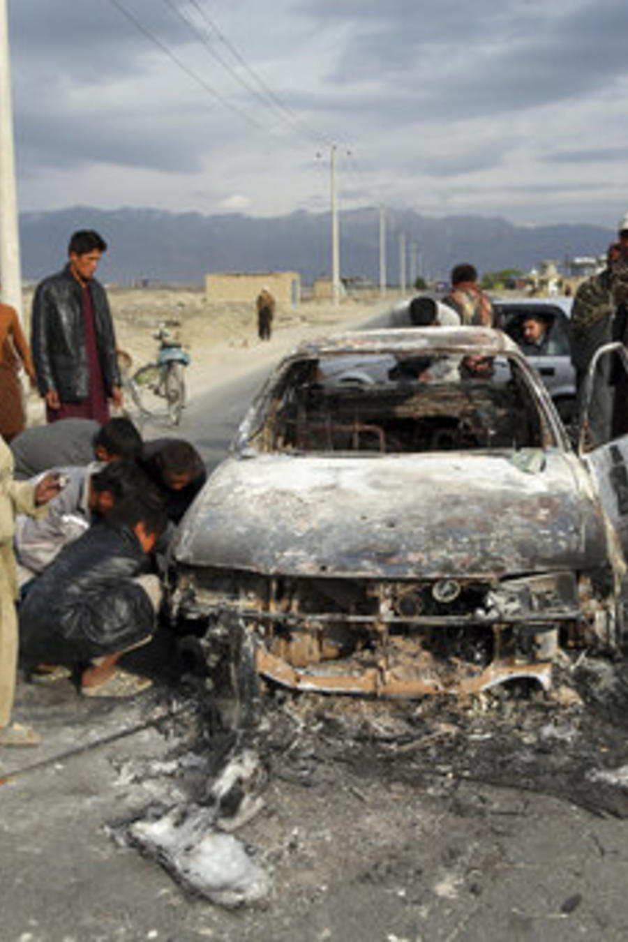 Afganos observan un vehículo civil quemado después de ser disparado por las fuerzas estadounidenses después de un ataque cerca de la base aérea de Bagram, al norte de Kabul, Afganistán, el martes 9 de abril de 2019. (AP/Rahmat Gul)