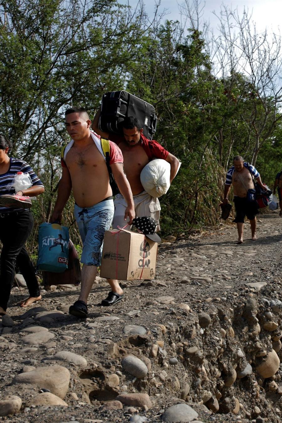 Grupo de venezolanos cargan sus pertenencias hacia Colombia, a través del río Táchira, el 25 de agosto de 2018.