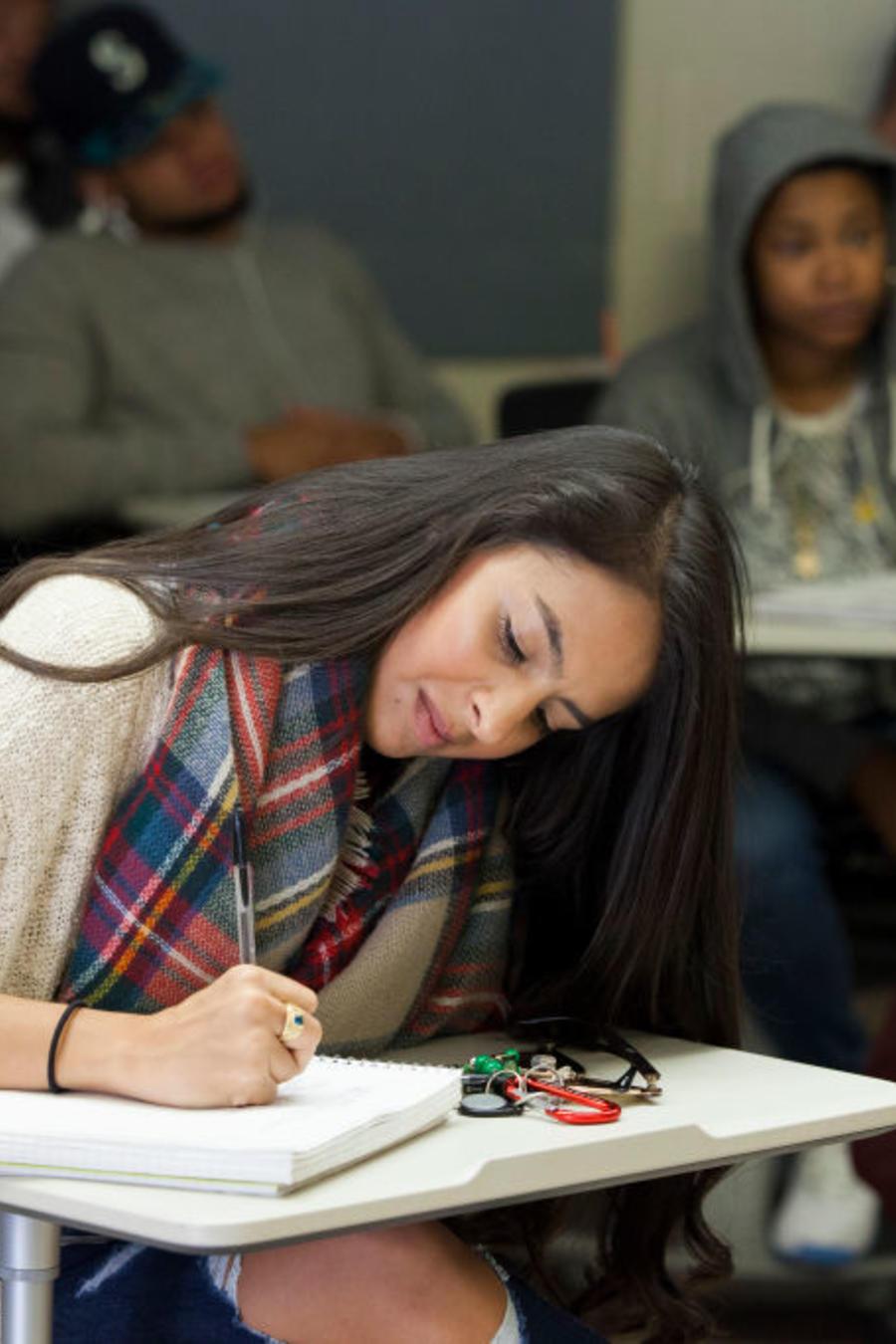 Estudiante universitaria toma notas durante una clase.