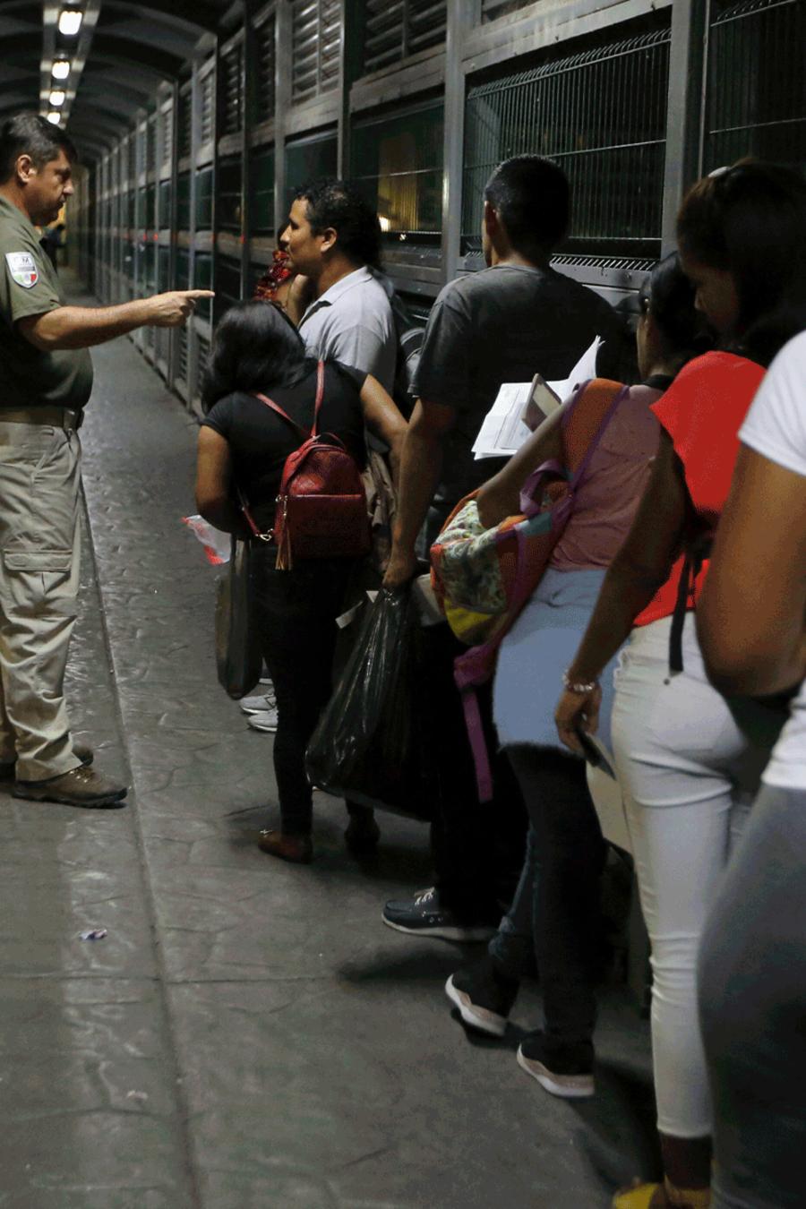 Un agente de Inmigración da órdenes a inmigrantes que esperan en fila para pedir asilo en Estados Unidos.