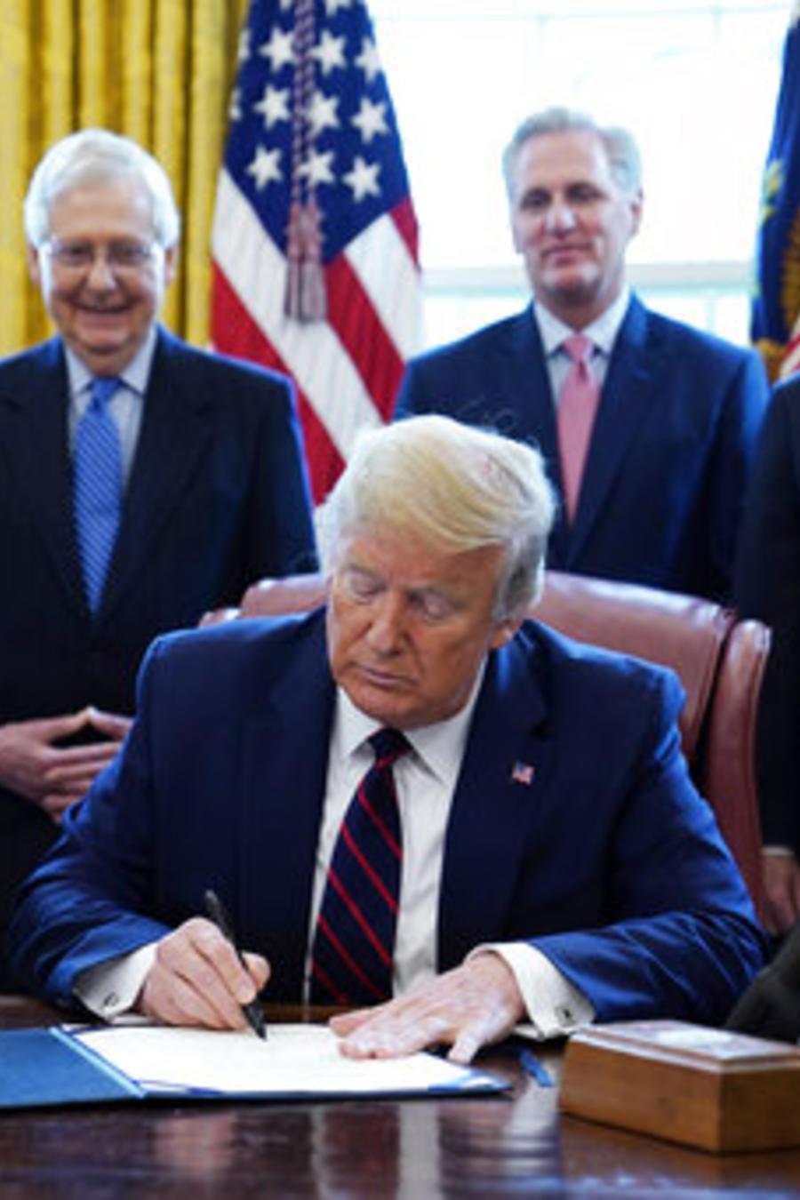 El presidente Donald Trump firma el paquete de alivio económico para aliviar la crisis creada por el coronavirus.