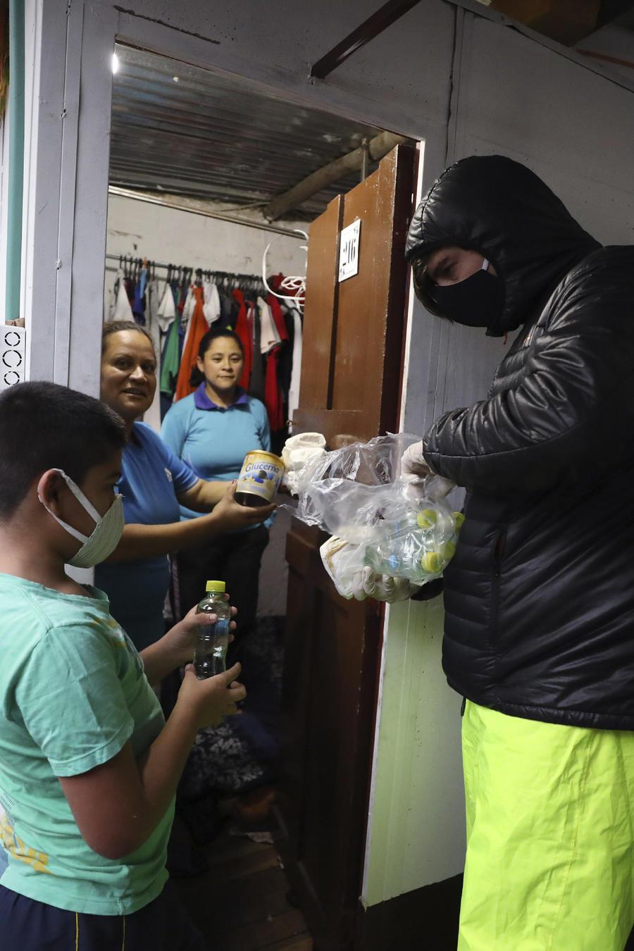 Emiliano Moscoso (der) entrega hamburguesas a una familia venezolana en un barrio pobre de Bogotá que pasan aún más necesidad por la pandemia del coronavirus, el 30 de marzo del 2020.