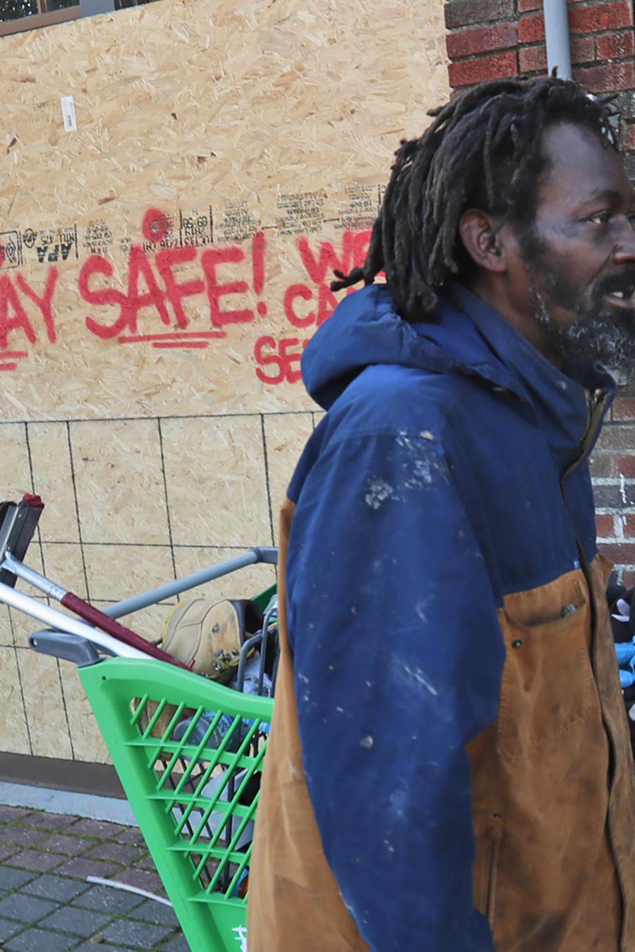 Vincent Amos, quien se identifica como una persona en situación de calle, pasa frente a un local comercial cerrado por el coronavirus.