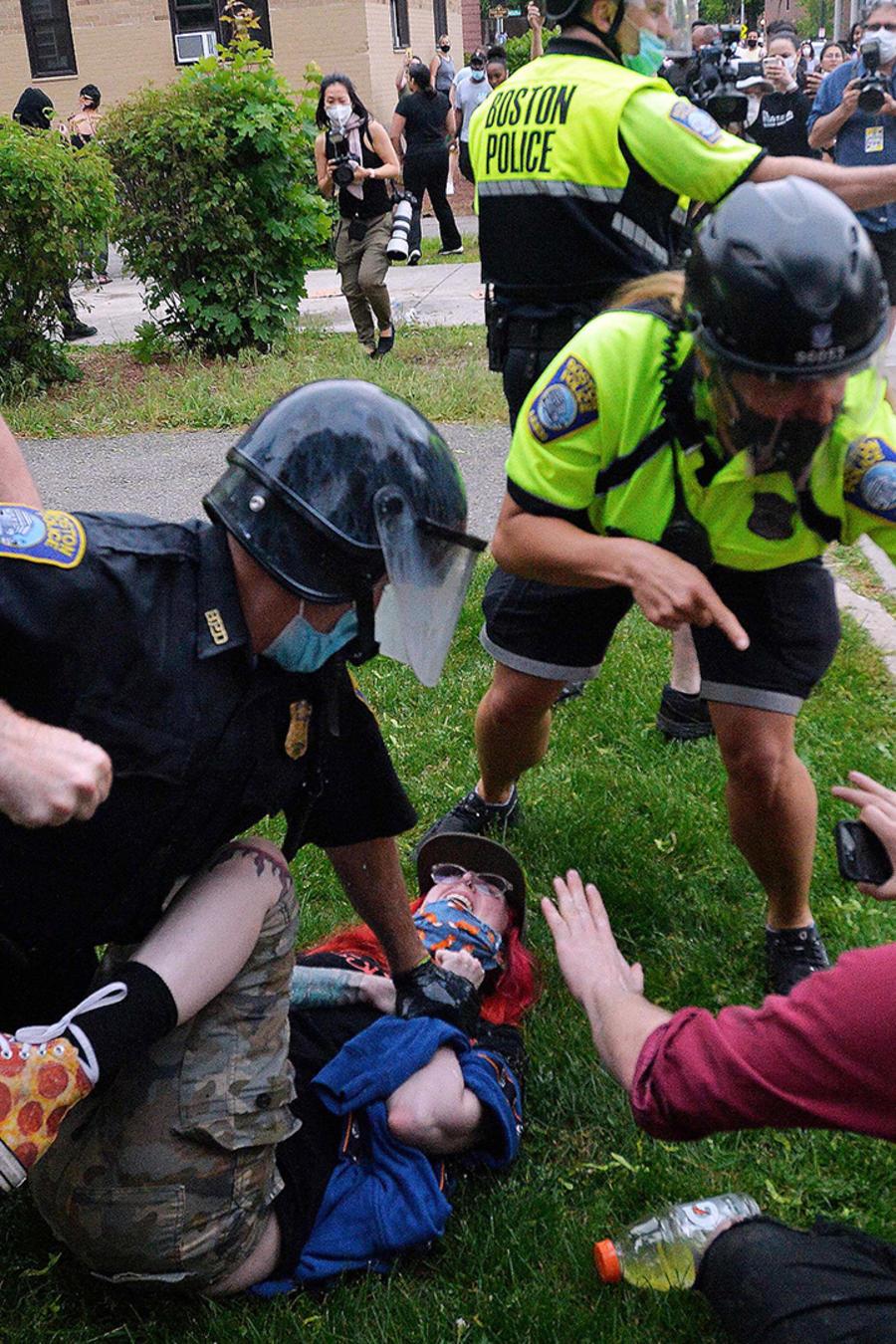 Un oficial de policía detiene a un manifestante mientras otro le rocía gas pimienta fuera de la estación de policía del Distrito Cuatro en Boston, Massachusetts, el 29 de mayo, durante una protesta contra la brutalidad policial y el racismo en EE.UU., inc