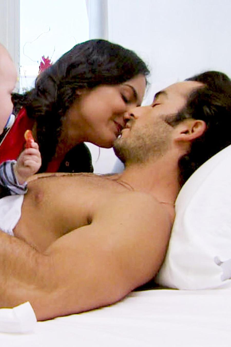Ana Lorena Sánchez y Aarón Díaz besándose en la cama junto a su bebé en Tierra de Reyes