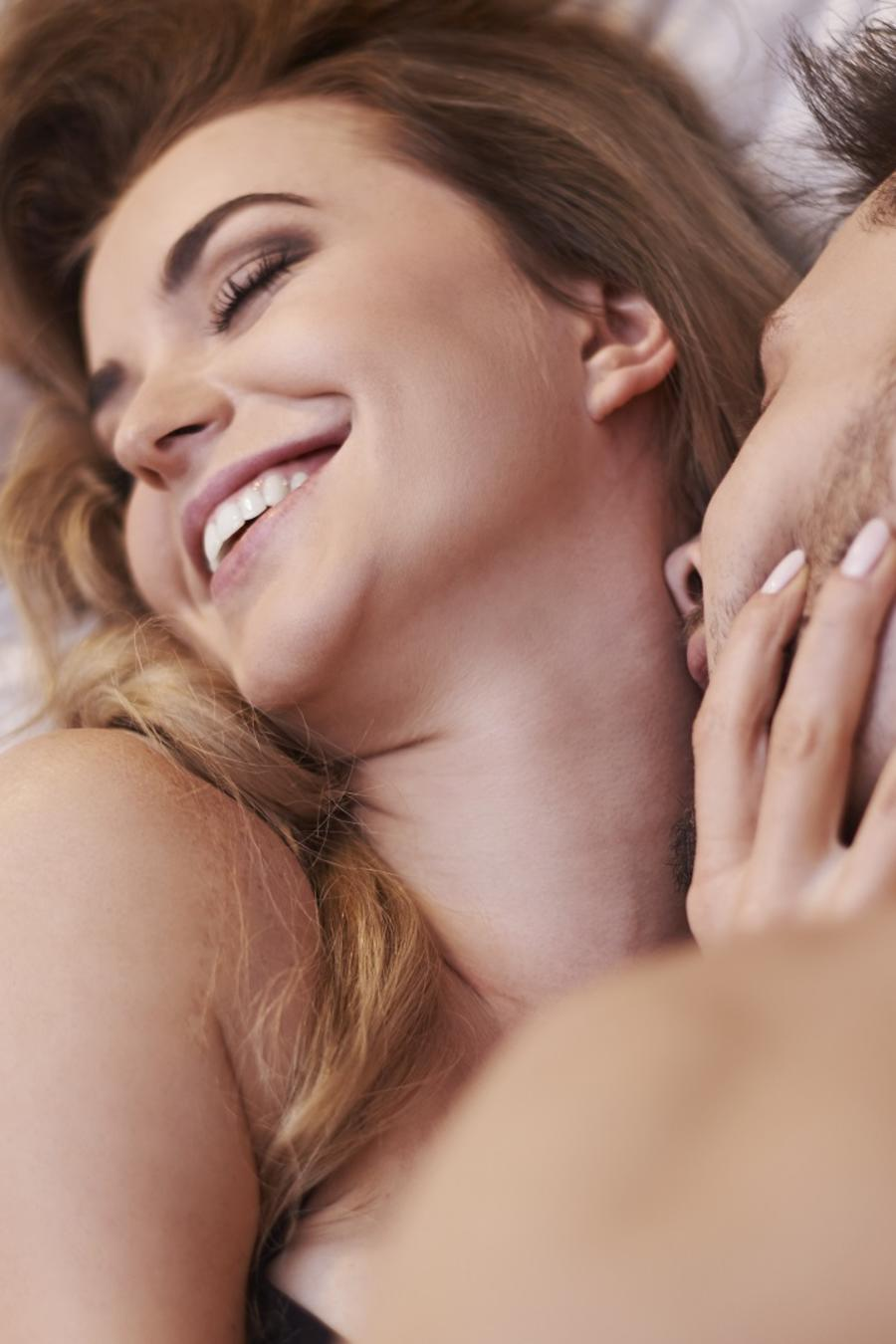 Mujer sonriendo en la cama mientras un hombre besa su cuello