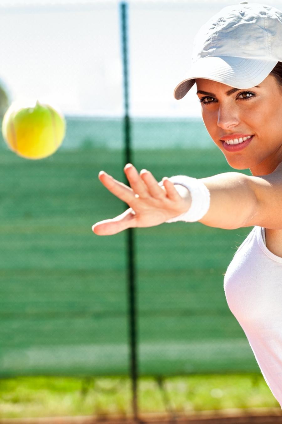 Mujer con gorra y blusa blanca jugando al tenis