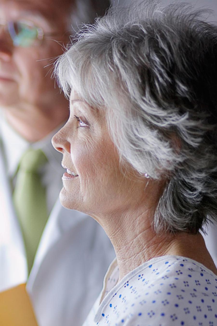 Mujer madura con médico frente a una mamografía