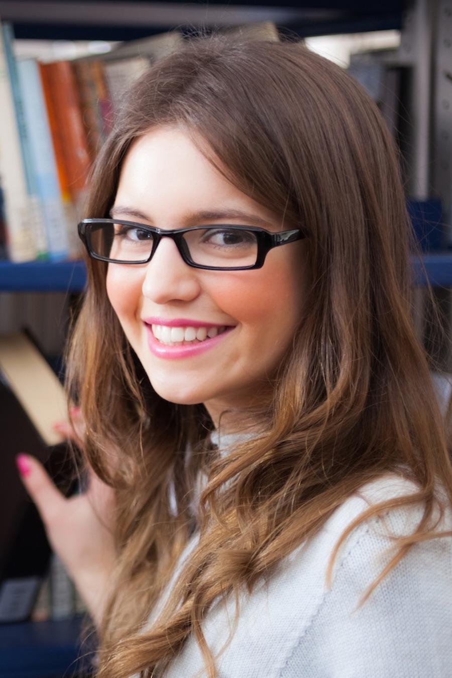 Chica tomando un libro en la biblioteca