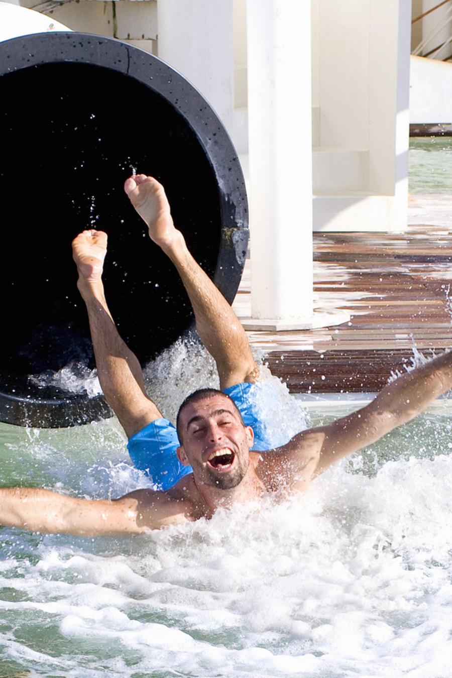 Hombre joven cayendo por un tobogán de agua