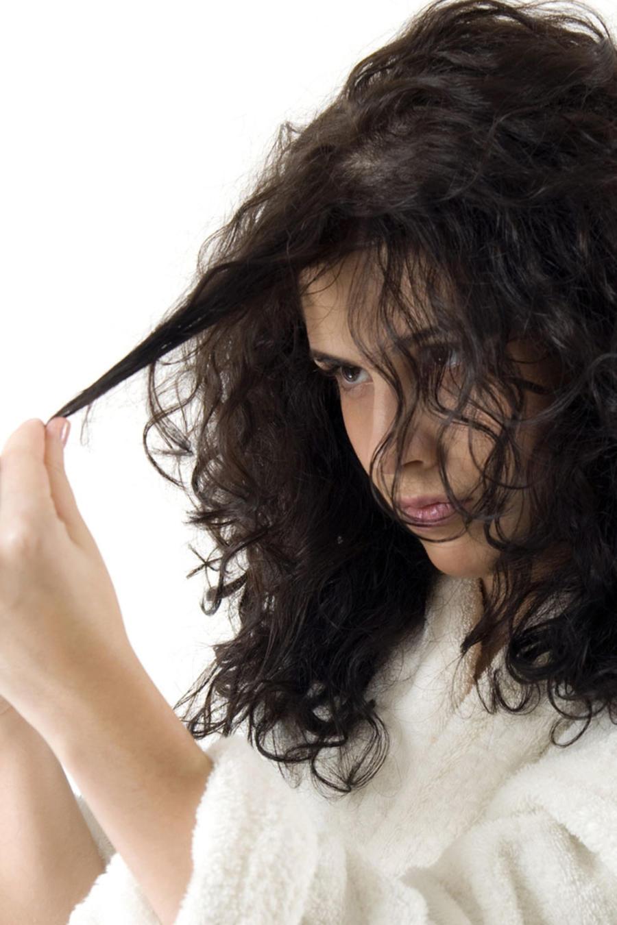 Mujer en bata mirándose el cabello