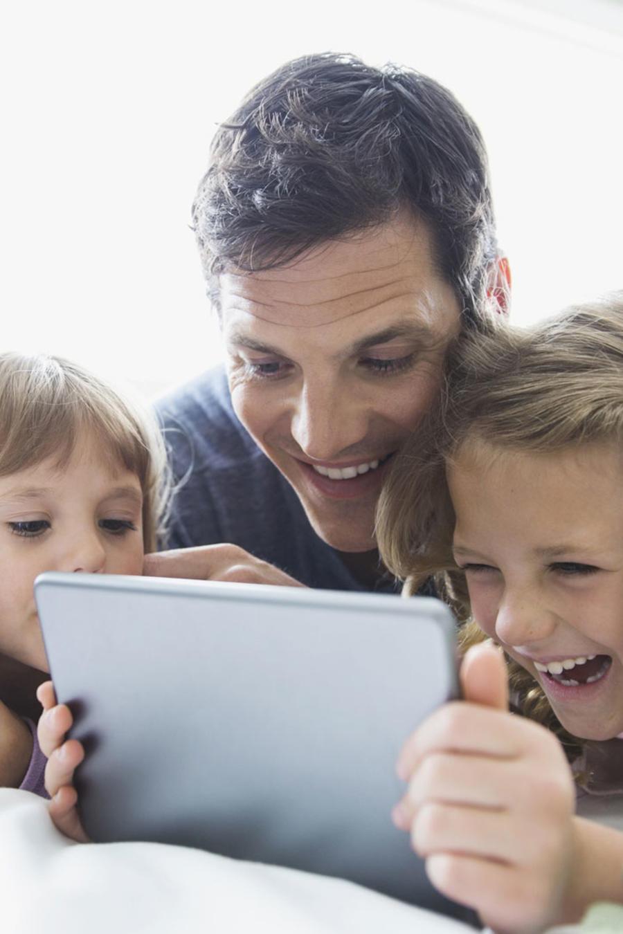 Familia usando una tablet en la cama