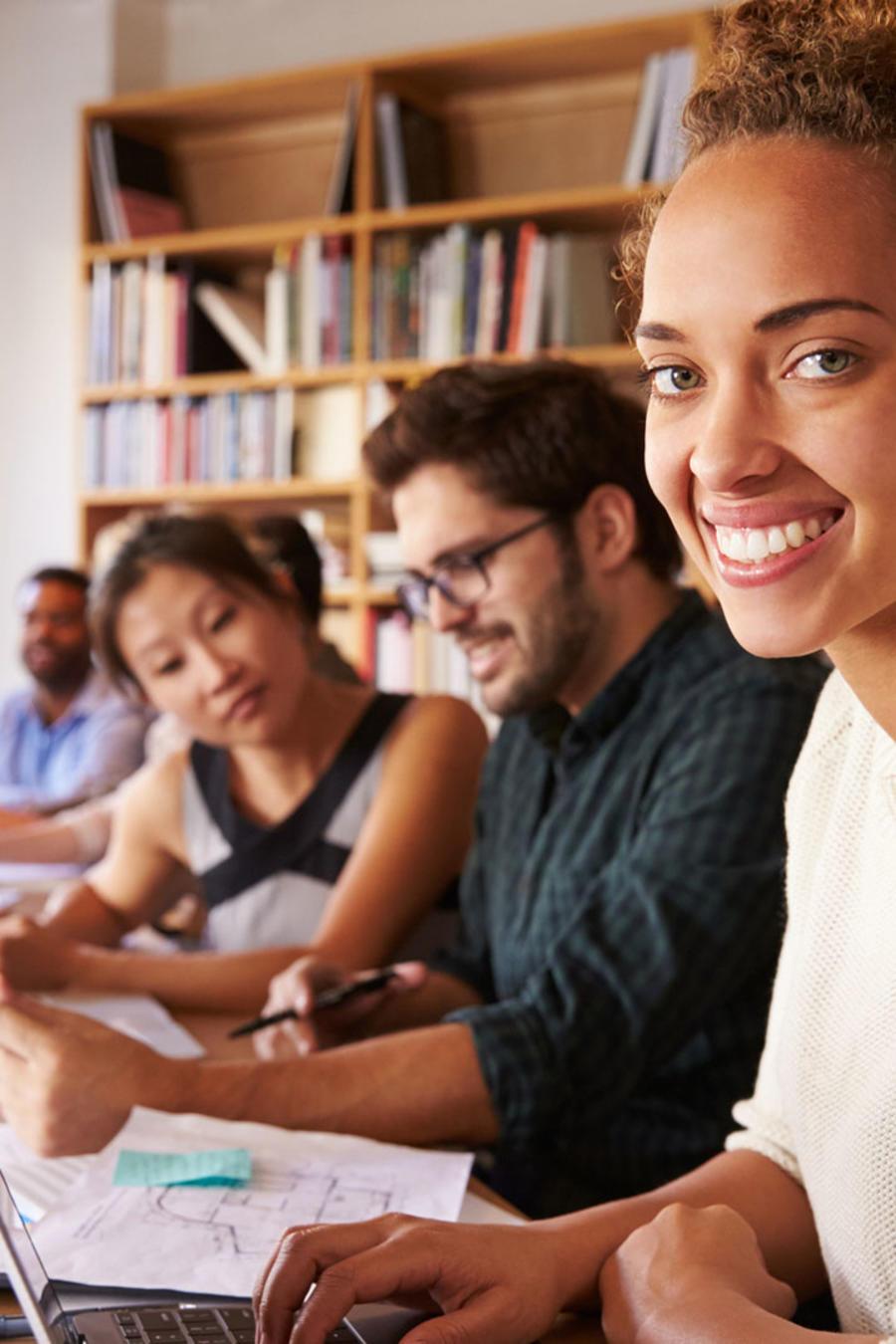 Mujer en la oficina sonriendo frente a laptop
