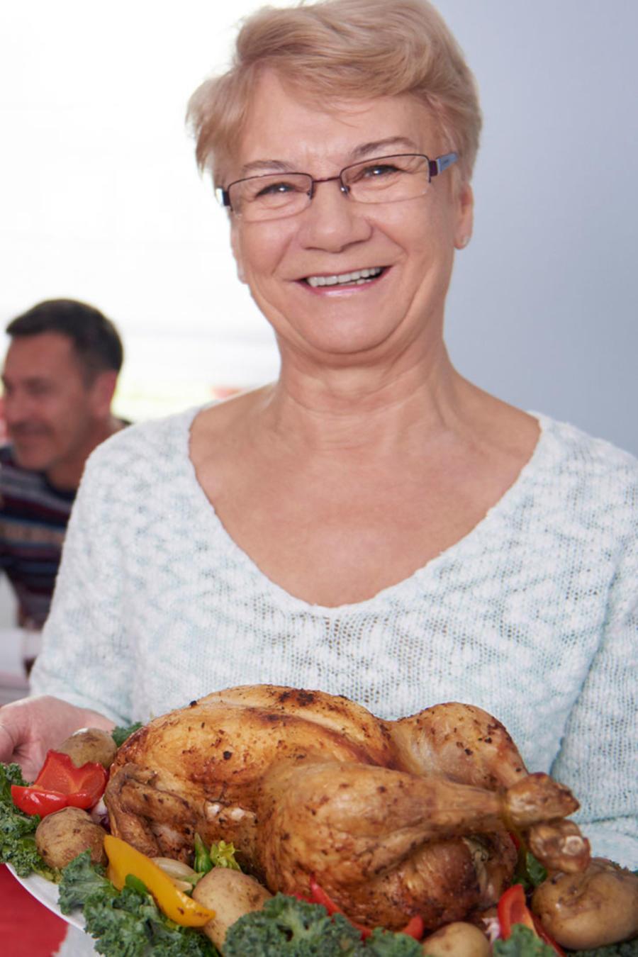 Abuela enseñando una bandeja con pollo durante cena navideña