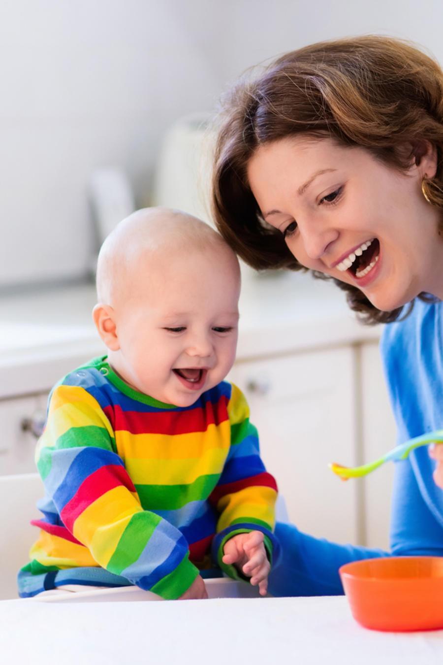 Madre dándole a su bebé de comer zanahorias