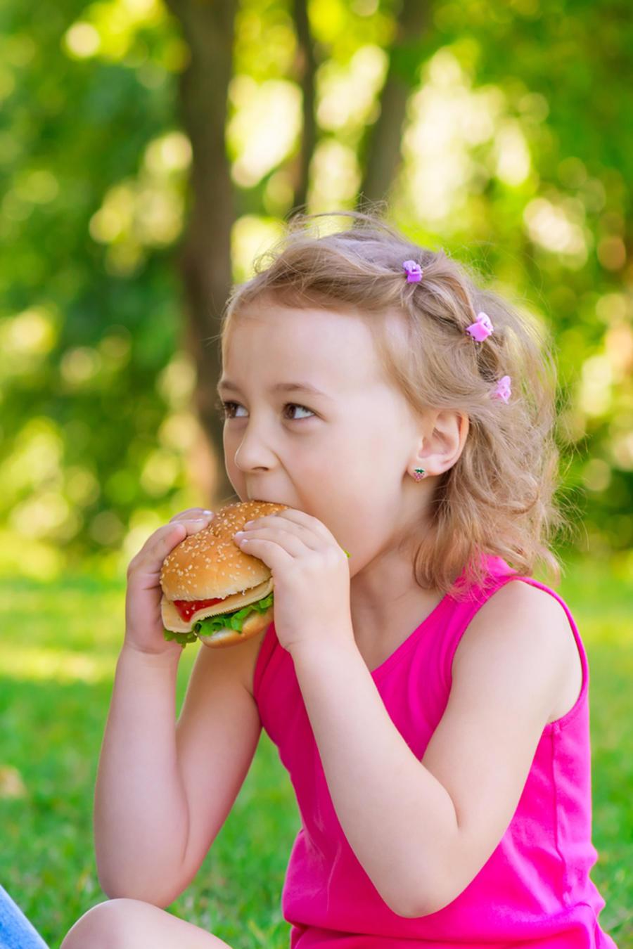 Madre e hija comiendo sandwiches en un picnic