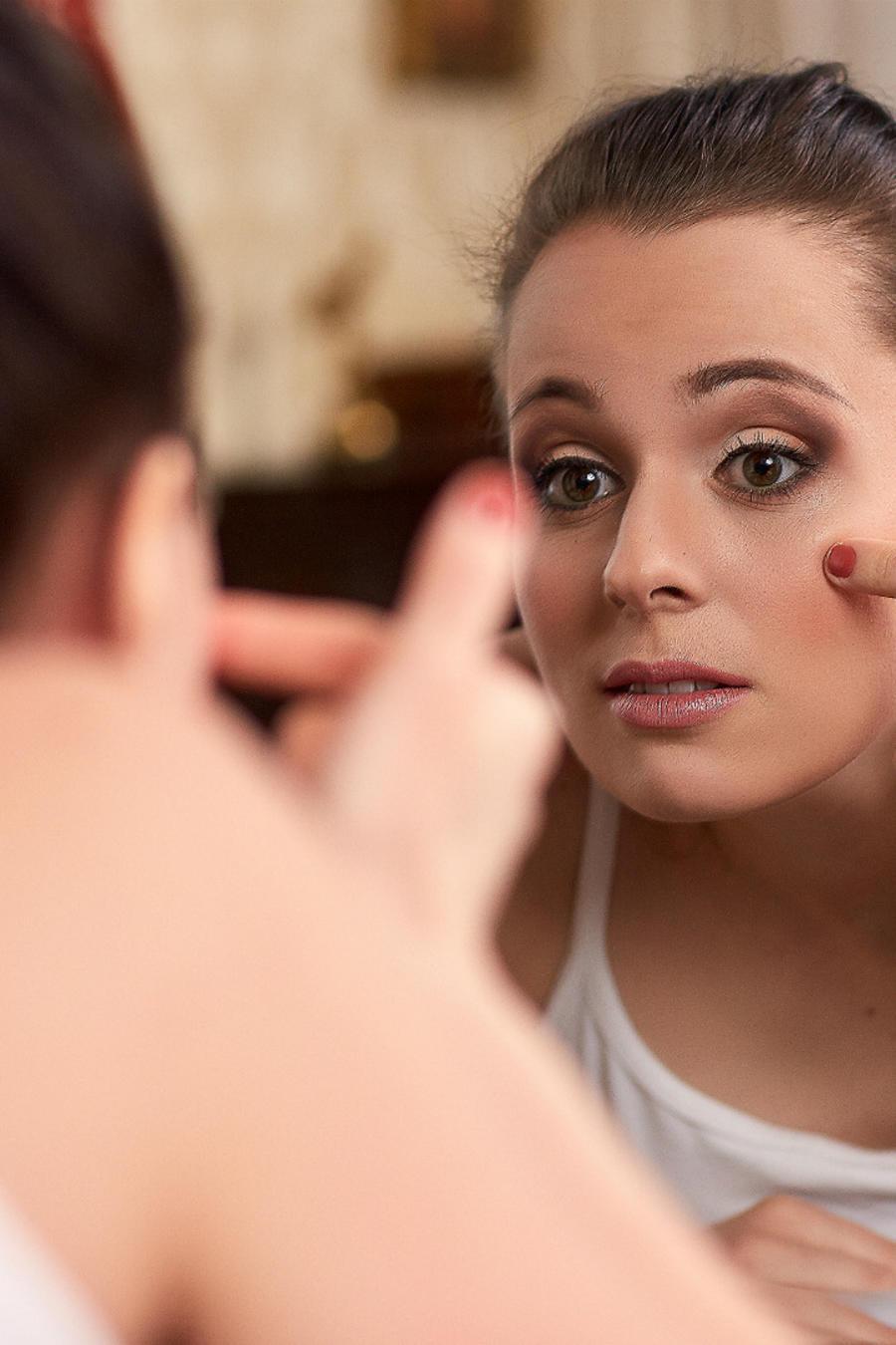 Mujer triste viendo un granito en el espejo.