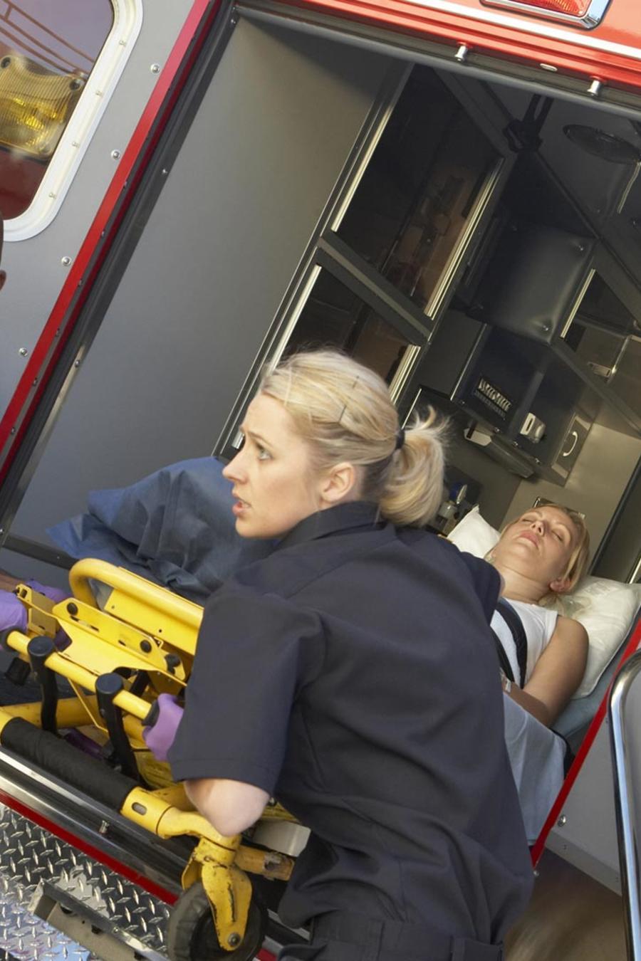 Paramédicos bajando una mujer de la ambulancia