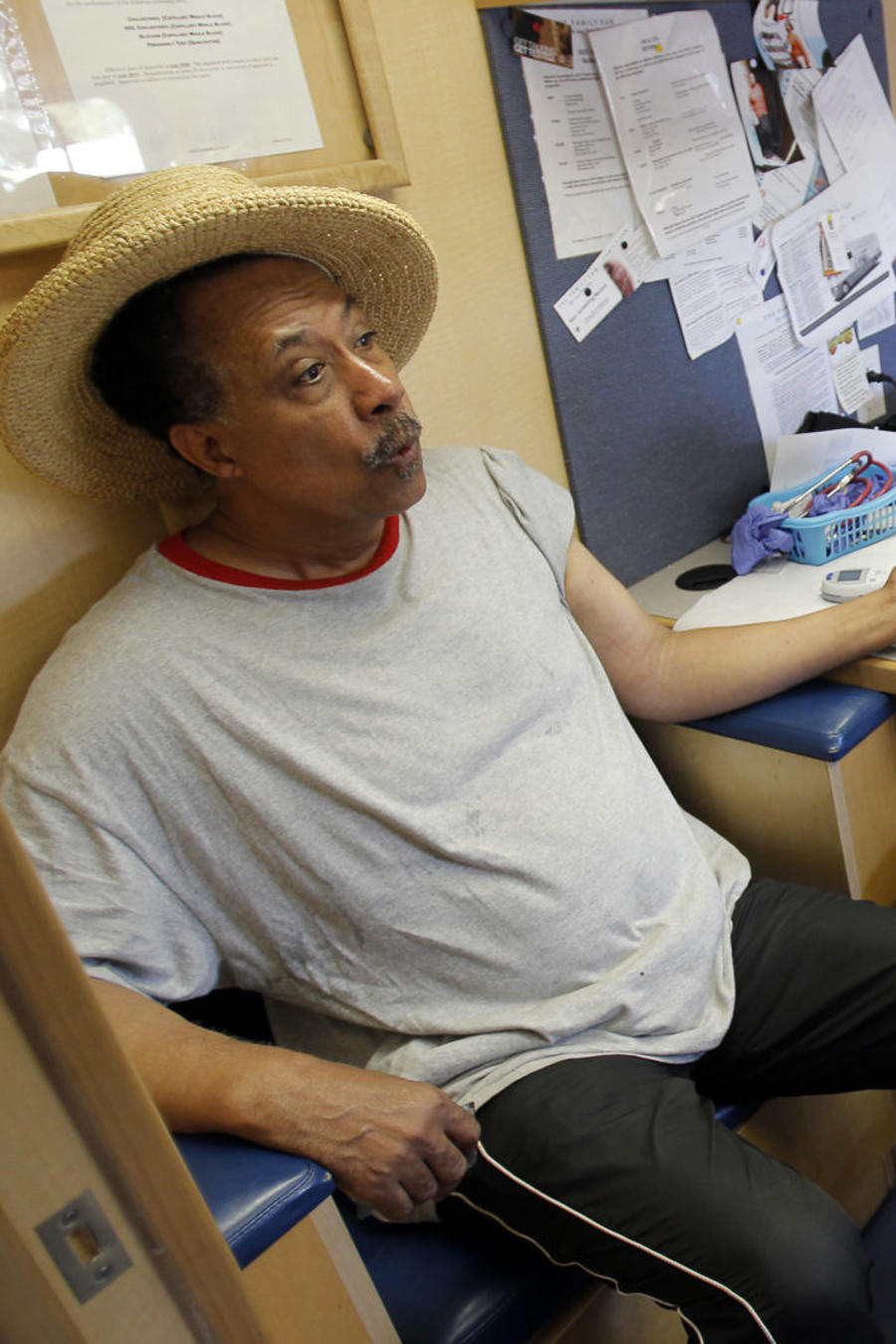 Client Dudley reacts as volunteer Pierre-Paul picks his finger for a cholesterol test in the Family Van in Boston