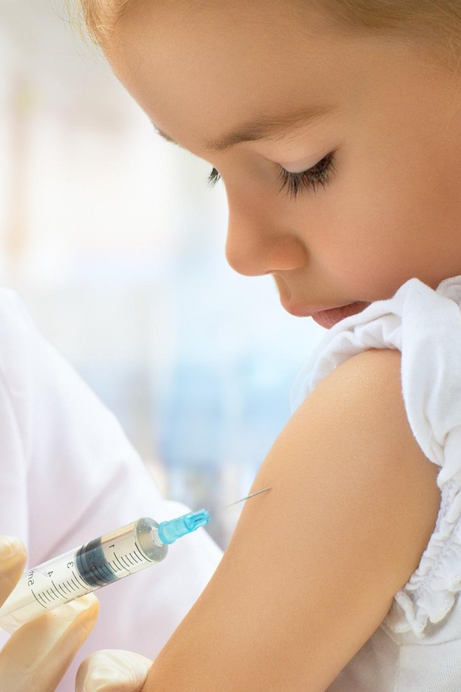 Médica dando vacuna a niña pequeña
