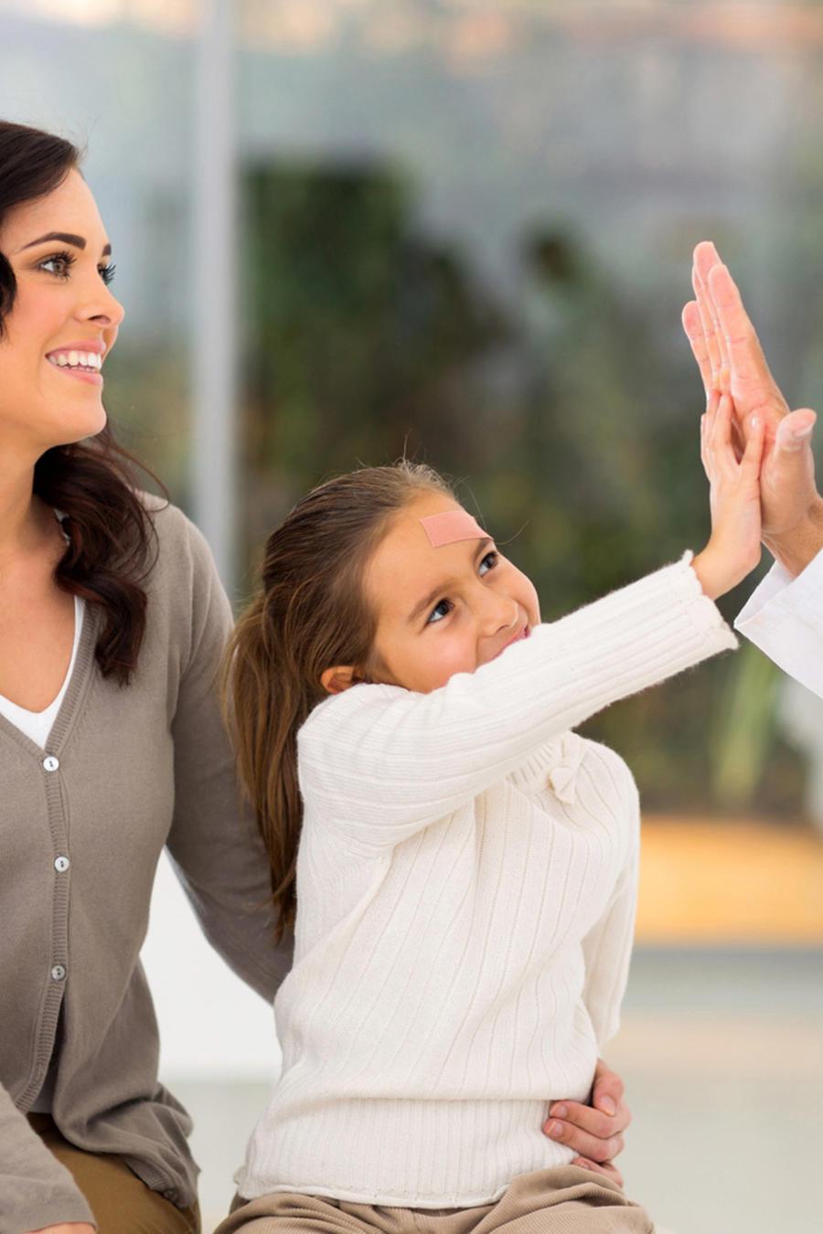 Pediatra chocando las manos con una niña