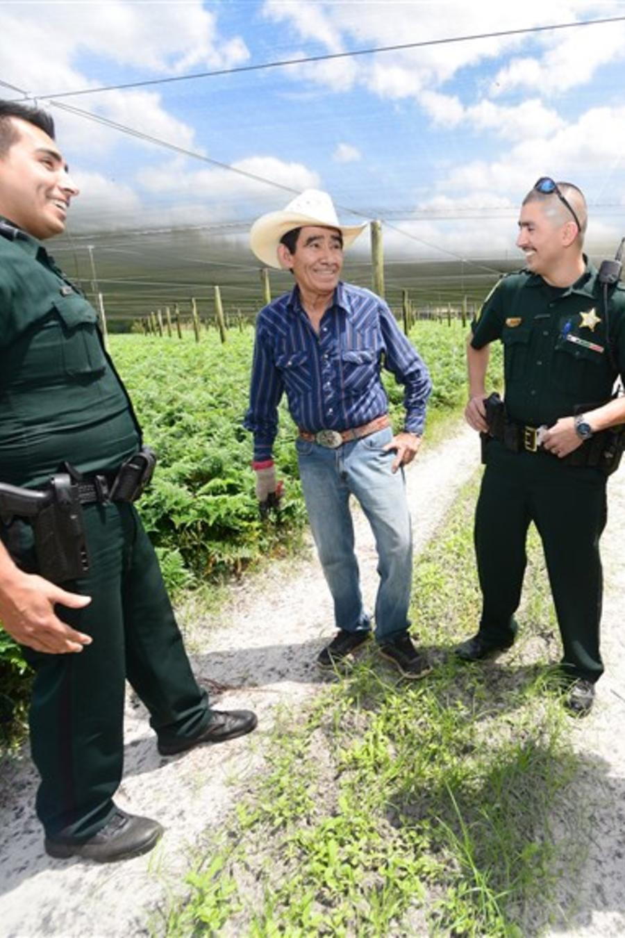 Pantaleon Galarza, un trabajador inmigrante de México, habla con sus tres hijos, Daniel, Roy y Billy Galarza, en una granja el 12 de abril de 2018 en el condado de Volusia, Florida.