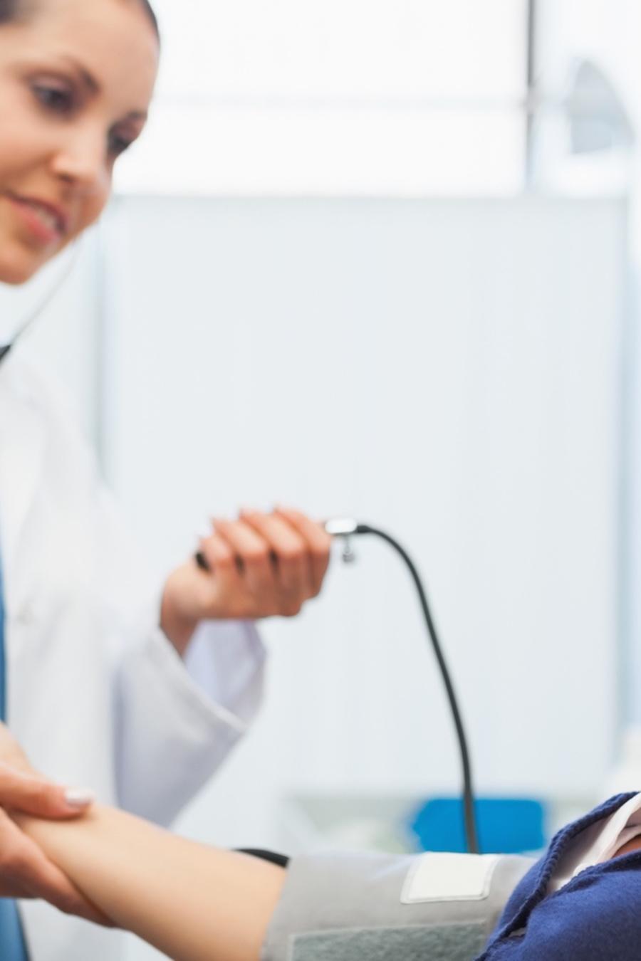 Médica tomando la presión de paciente