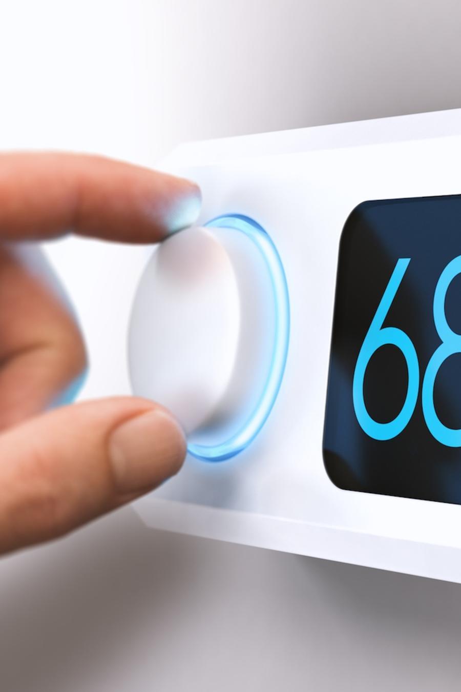 Mano ajustando termostato inteligente