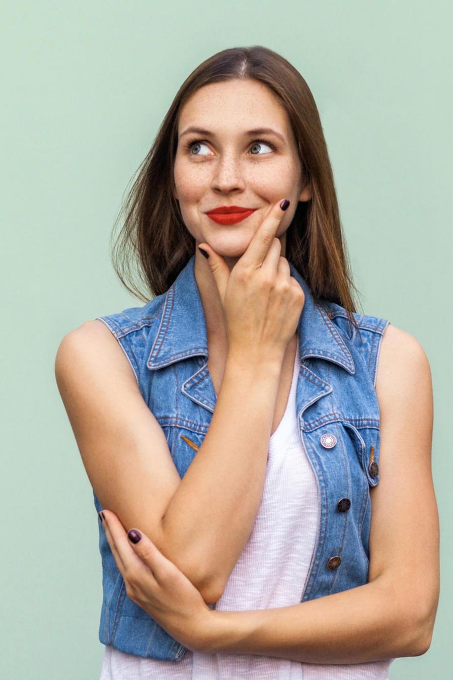Mujer joven sonriente, pensando
