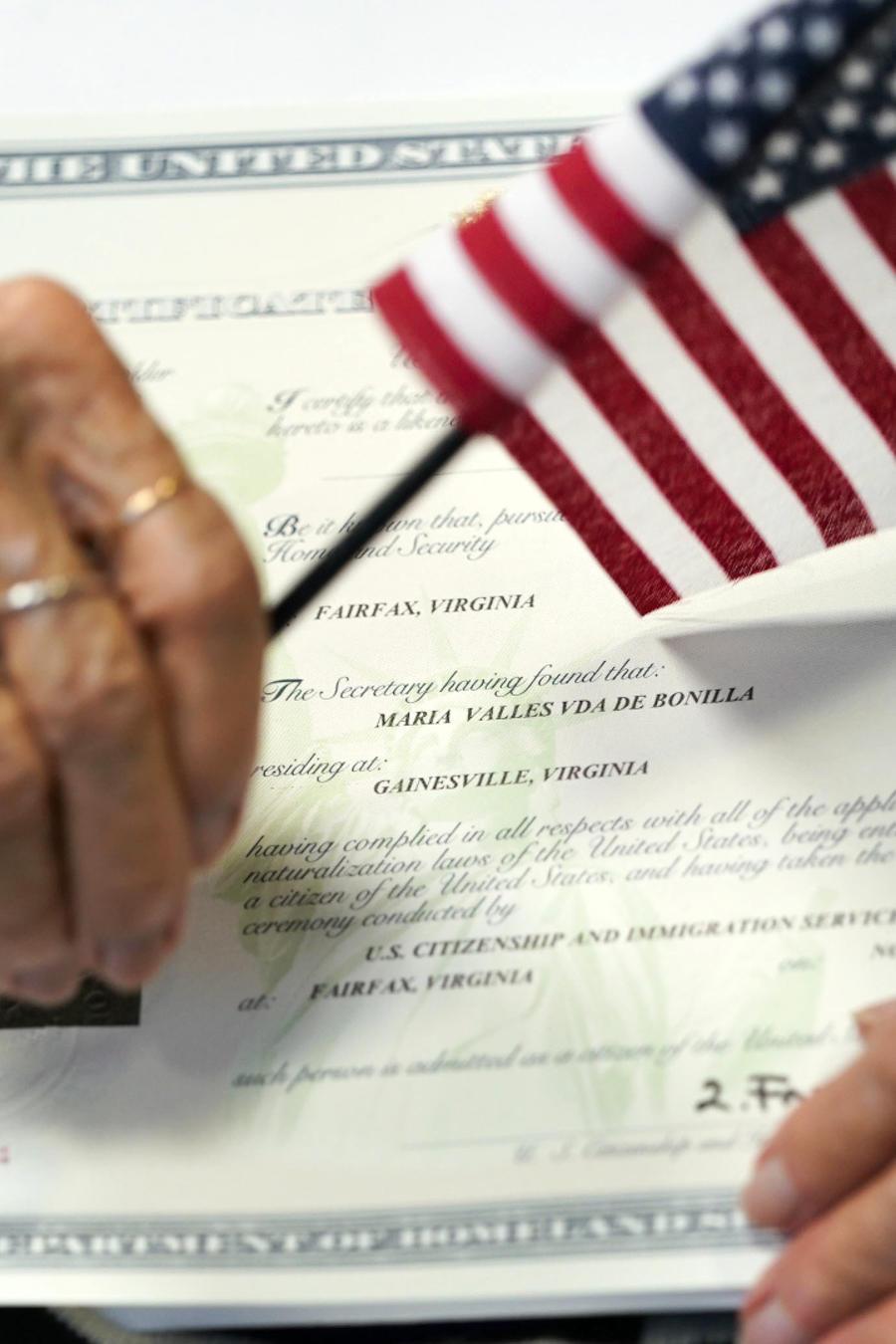 Imagen de archivo de una mujer sosteniendo una bandera de Estados Unidos y un certificado de naturalización