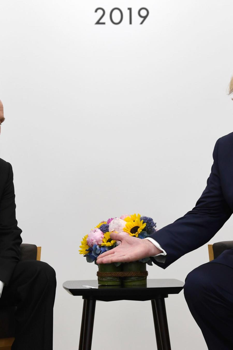 Trump (derecha) extiende la mano a Putin en su reunión de junio de 2019 en Japón.