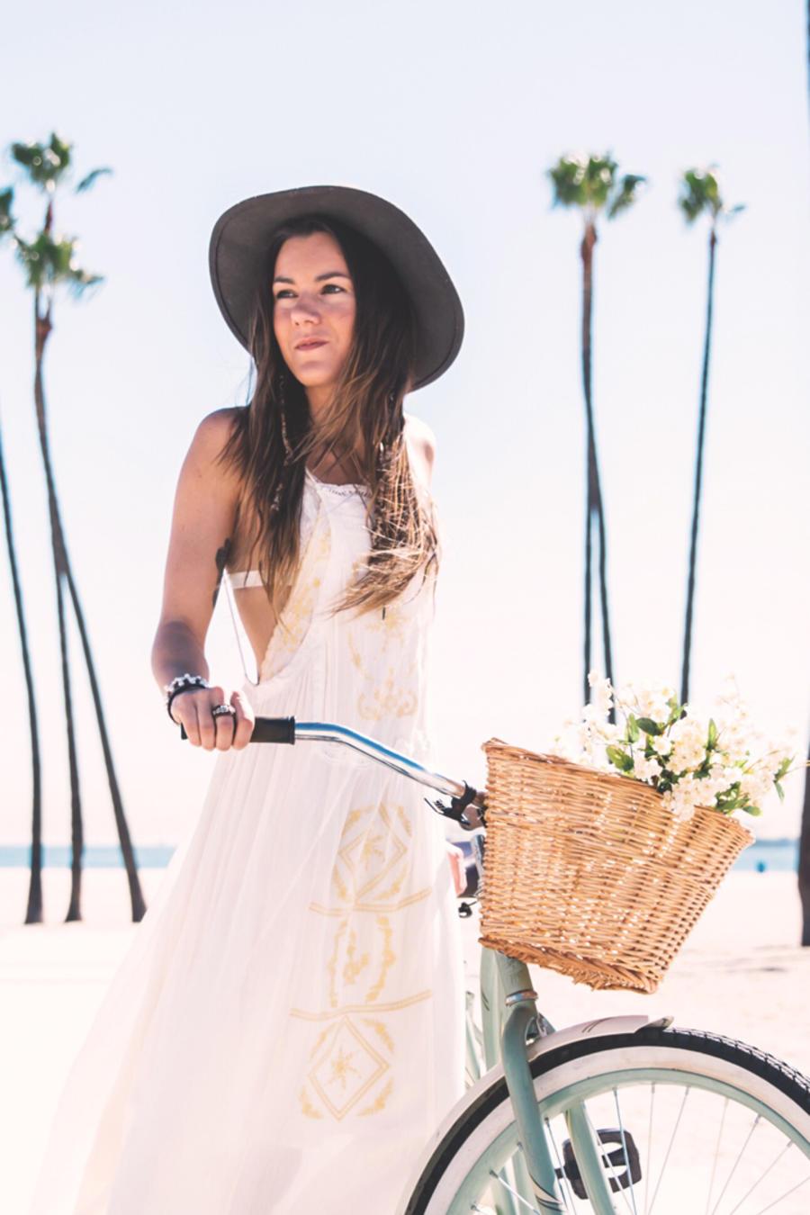 Chica con vestido y en bici en la playa