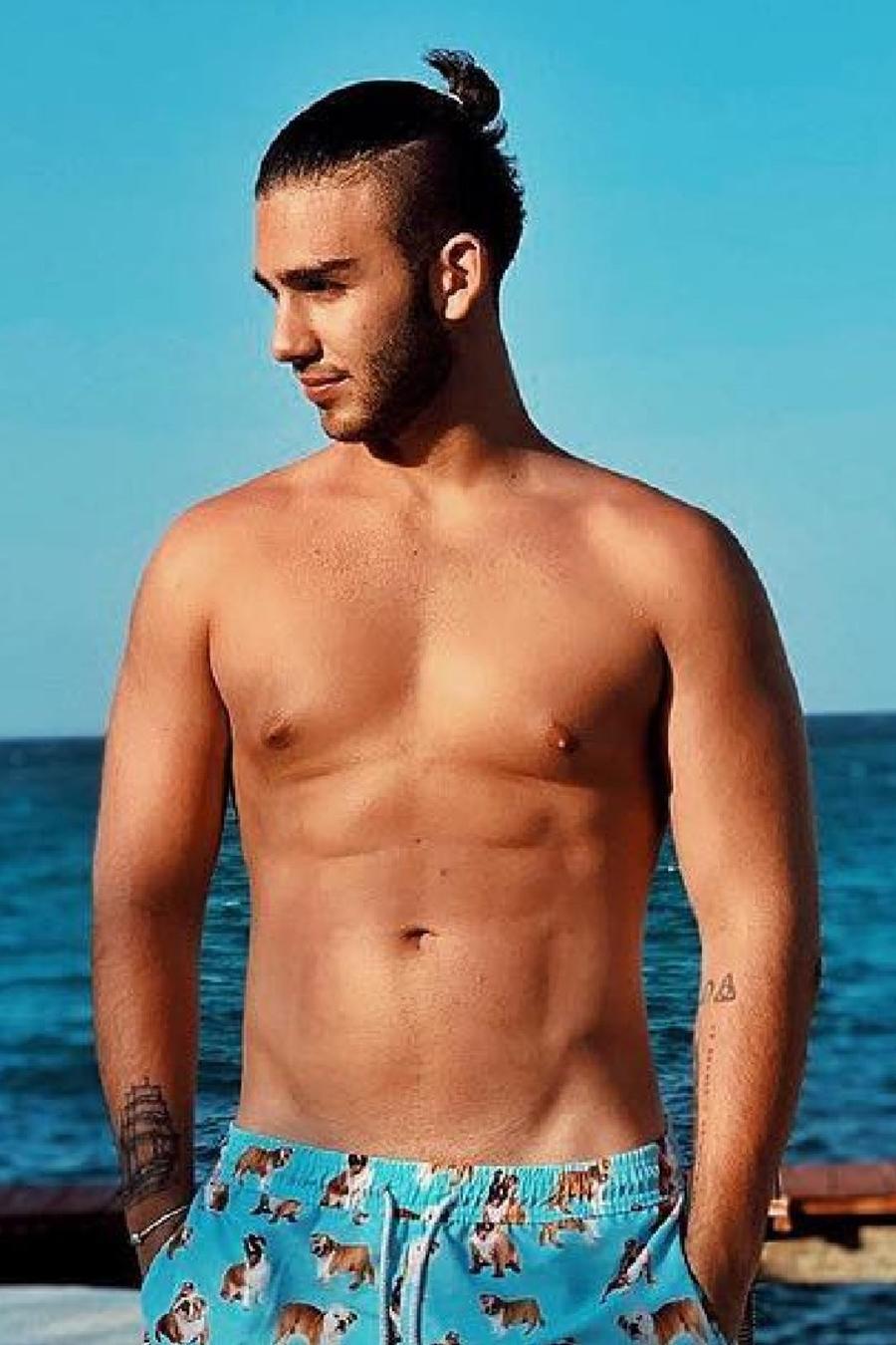 Manuel Turizo en la playa mostrando sus abs
