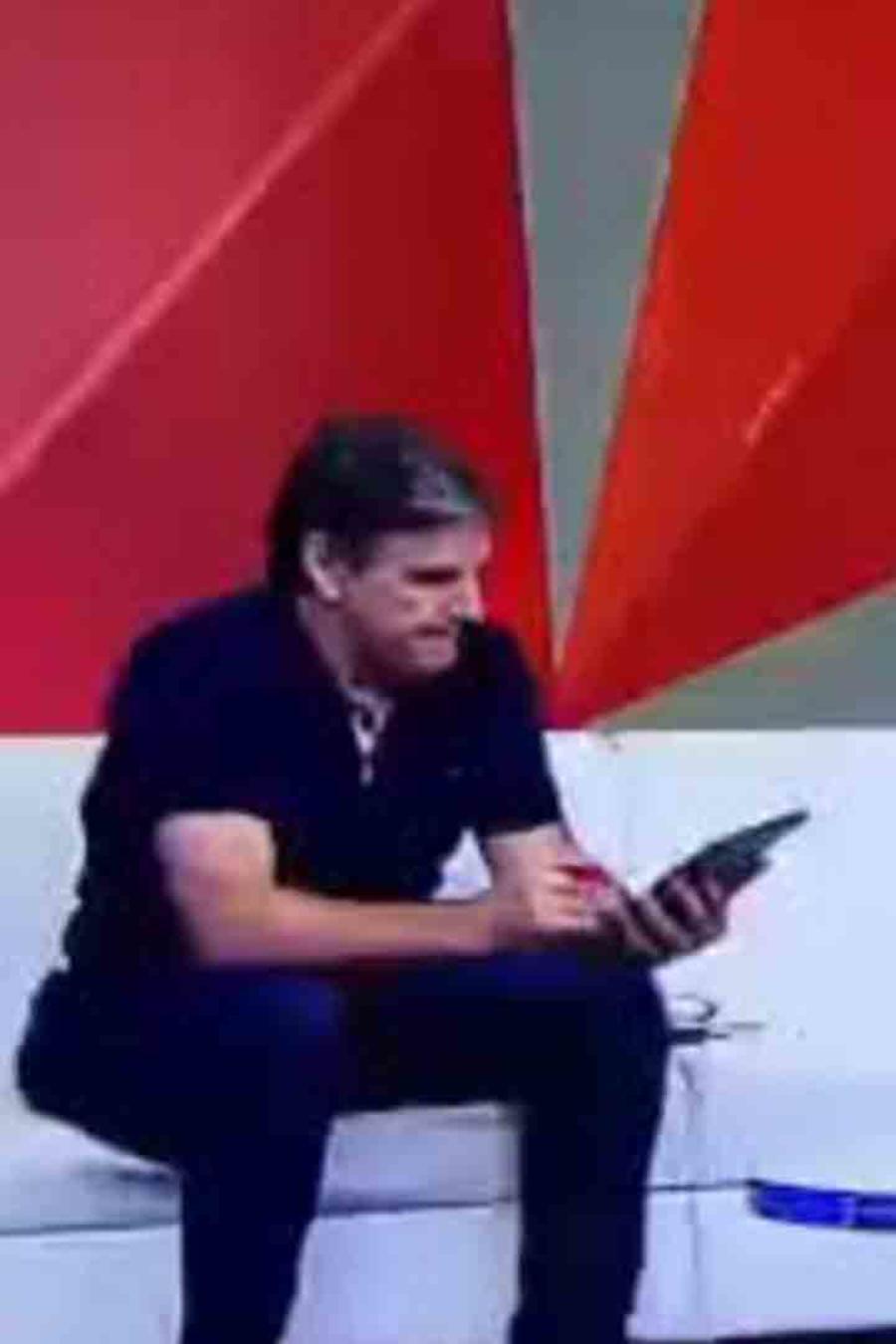 Presentador viendo el celular