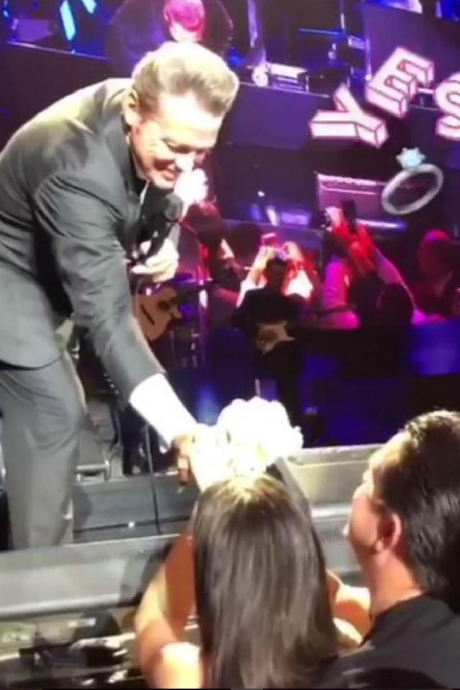 Luis Miguel entregando flores a una pareja