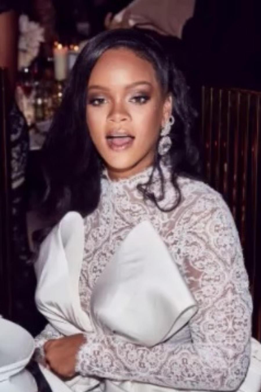 Rihanna sentada con un vestido blanco