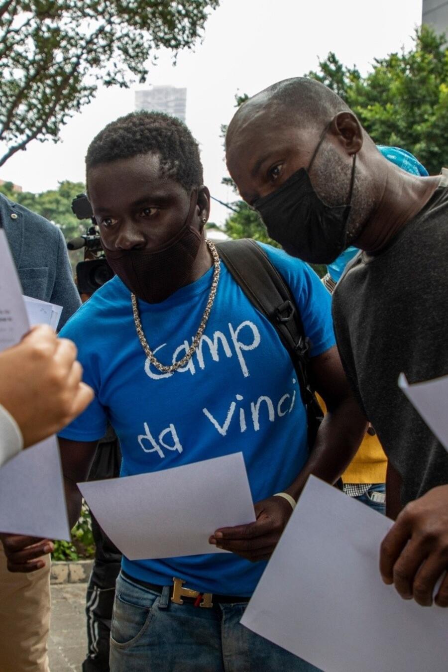 inmigrantes viendo papel.jpg