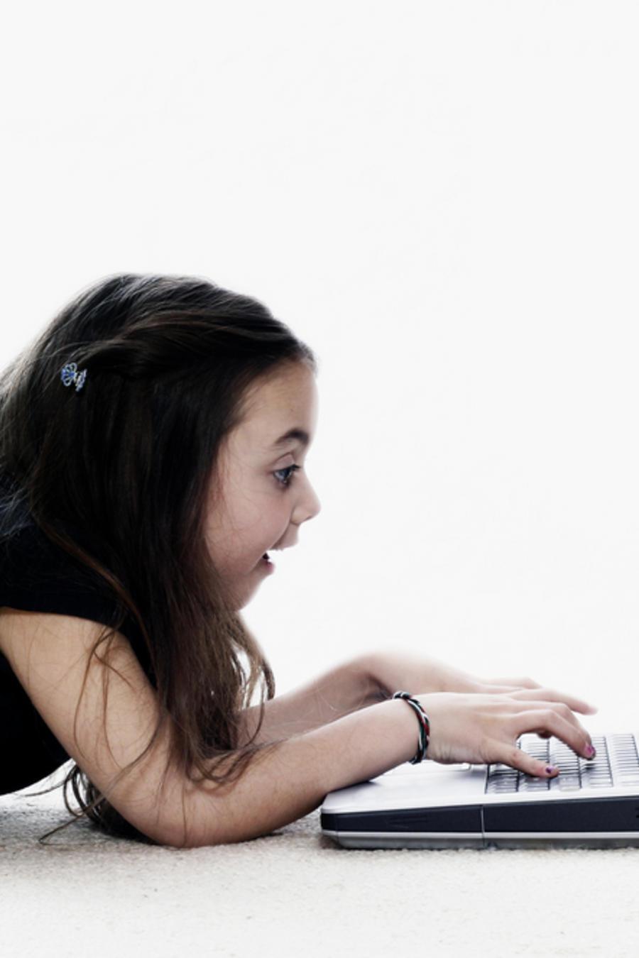 Niña acostada frente a un computador portátil