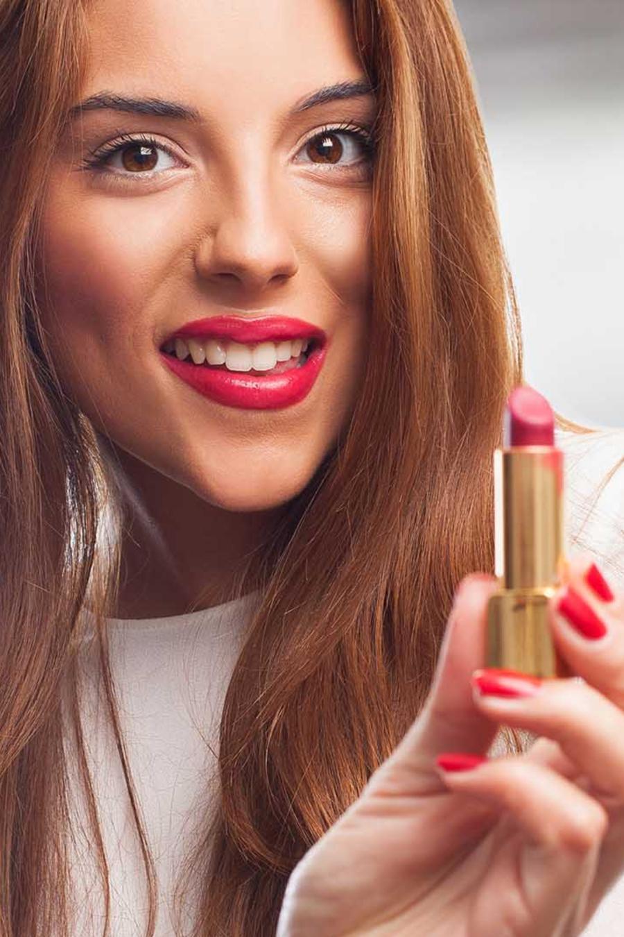 mujer con labios rojos sosteniendo un labial