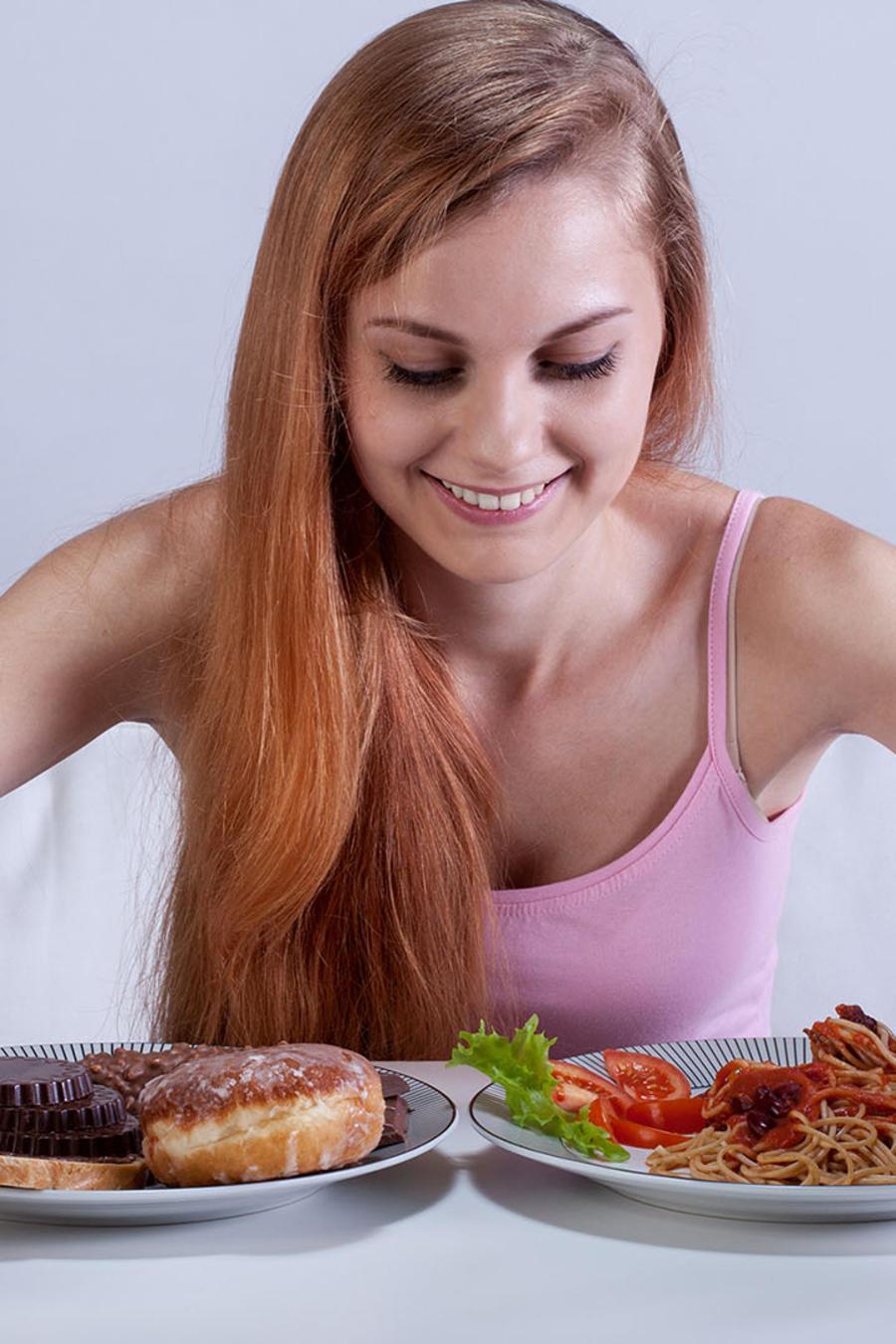 mujer con dos platos de comida en la cama