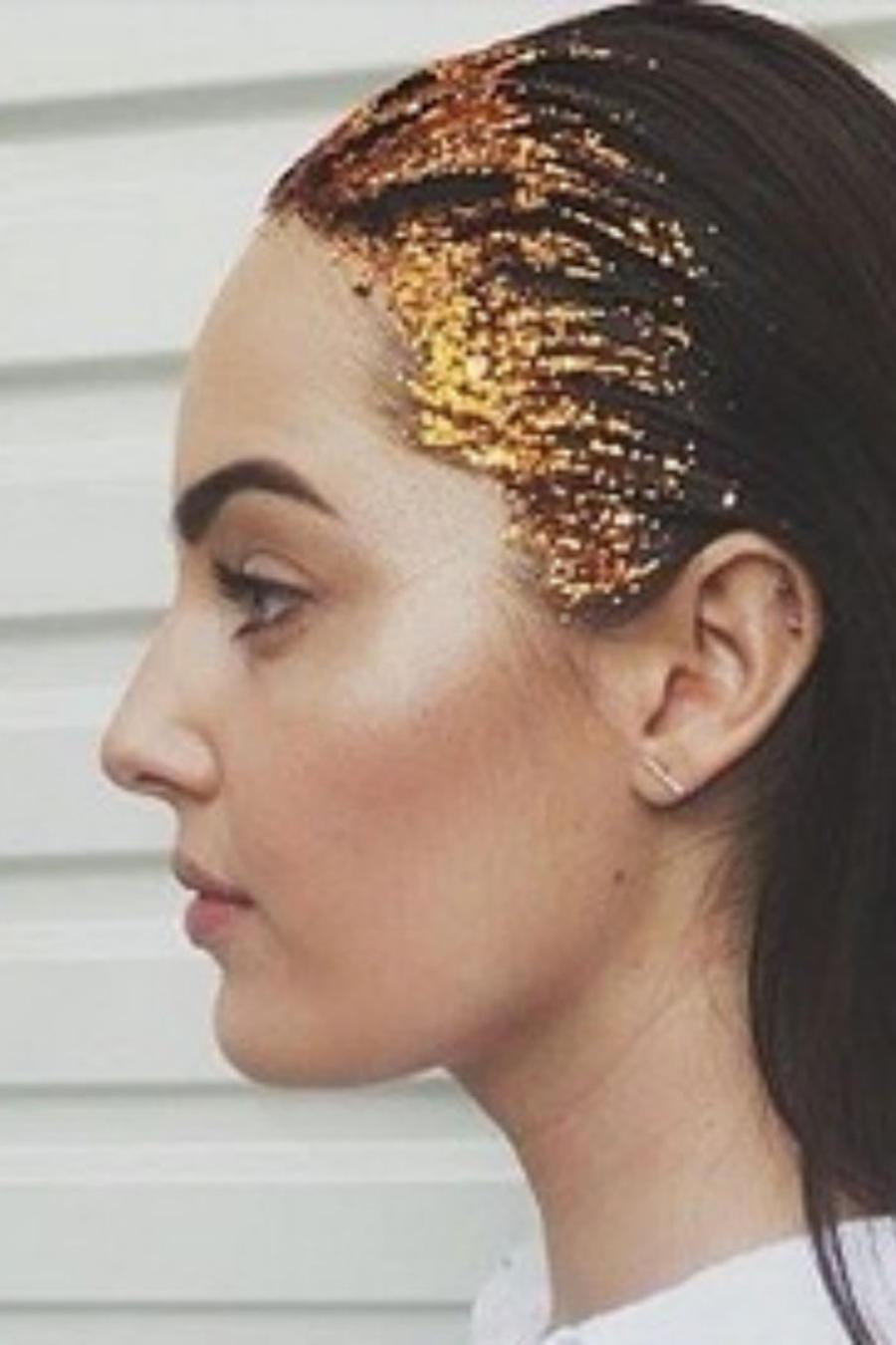 mujer con blusa blanca y brillantina dorada en su cabello