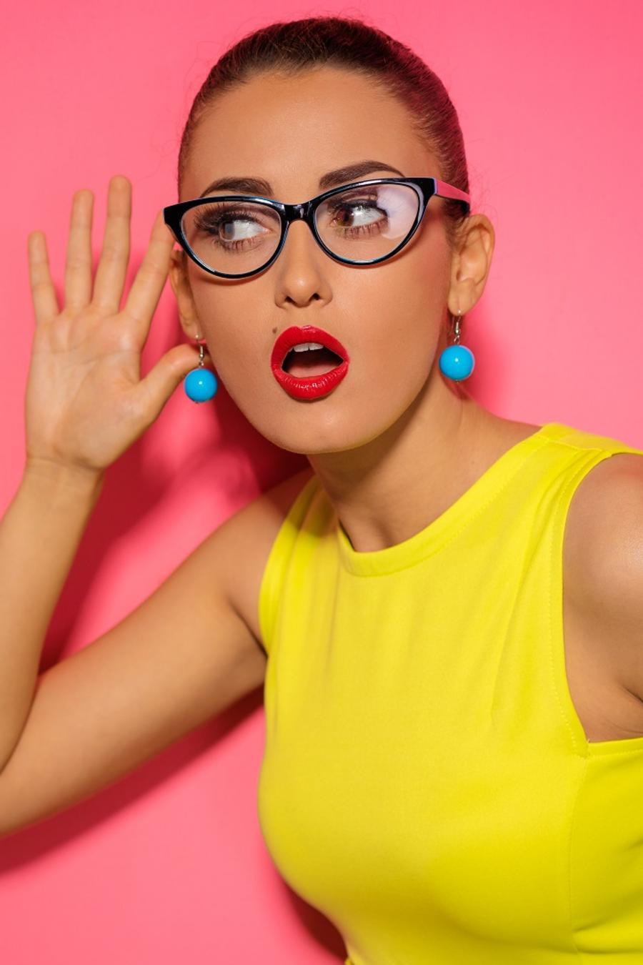 Mujer con vestido amarillo con una mano en el oido