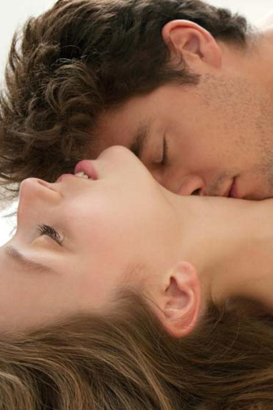 Hombre desnudo y mujer con sostén negro besándose en la cama