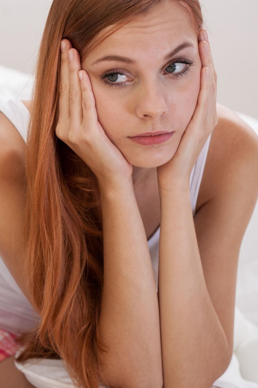 Mujer aburrida sentada sobre la cama mientras hombre duerme